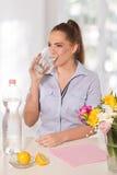 Den härliga unga kvinnan som dricker ett exponeringsglas av, bevattnar witthcitronen Royaltyfri Fotografi