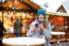 Den härliga unga kvinnan som dricker varm stansmaskin, funderat vin på tysk jul, marknadsför Lycklig flicka i vinterkläder med arkivbild