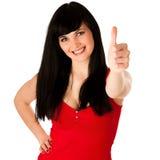 Den härliga unga kvinnan som gör en gest framgångvisning, tummar upp Fotografering för Bildbyråer
