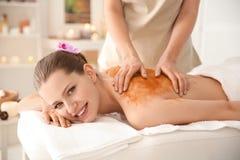 Den härliga unga kvinnan som har massage med kroppen, skurar royaltyfri bild
