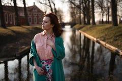 Den härliga unga kvinnan som kopplar av nära en kanalflod i, parkerar nära slotten i Rundale, Lettland, 2019 arkivbild