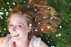 Den härliga unga kvinnan som ler med våren, blommar i hår Royaltyfri Fotografi