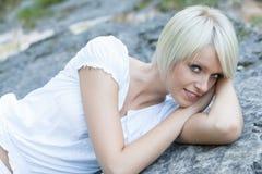 Den härliga unga kvinnan som ligger på en granit, vaggar royaltyfria foton