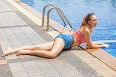 den härliga unga kvinnan som ner ligger, solbadar och avkoppling som utomhus poserar vid simbassängen in sexigt kvinnligt vila i  arkivfoto