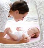 Den härliga unga kvinnan som ser, behandla som ett barn i säng Royaltyfri Fotografi