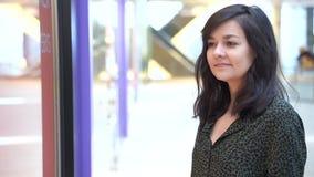 Den härliga unga kvinnan som ser i, shoppar fönstret i shoppinggalleria lager videofilmer