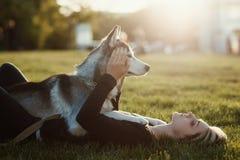 Den härliga unga kvinnan som spelar med den roliga skrovliga hunden i, parkerar utomhus på solnedgången eller soluppgång Arkivfoto