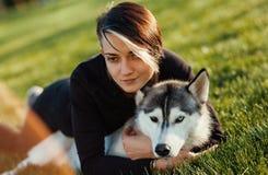 Den härliga unga kvinnan som spelar med den roliga skrovliga hunden med olika ögon på, parkerar utomhus på grönt gräs Arkivbilder