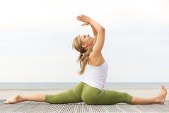 Den härliga unga kvinnan som sträcker yoga, poserar på stranden Arkivbild