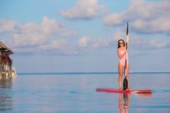 Den härliga unga kvinnan som surfar på, står upp skoveln Arkivfoto