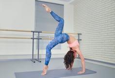 Den härliga unga kvinnan som utarbetar i konditiongrupp och att göra yogaövning på mattt, sträckning som står i bro, poserar Fotografering för Bildbyråer
