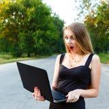 Den härliga unga kvinnan stirrar på en bärbar dator medan Arkivbilder
