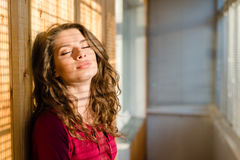 Den härliga unga kvinnan synar den stängda flickan med skugga från fönsterrullgardiner Arkivfoton