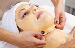Den härliga unga kvinnan tar bort den ansikts- maskeringen i en skönhetmitt royaltyfri foto