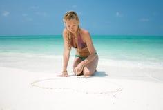 Den härliga unga kvinnan tecknar hjärta royaltyfri fotografi