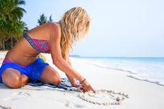Den härliga unga kvinnan tecknar hjärta på sanden fotografering för bildbyråer
