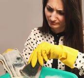 Den härliga unga kvinnan tvättar skuggiga pengar (olaglig kassa, dollar arkivfoto