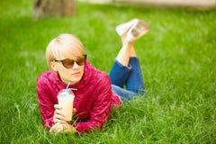 Den härliga unga kvinnan tycker om att dricka kaffe och att ligga på gräset Fotografering för Bildbyråer