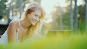 Den härliga unga kvinnan tycker om en bärbar dator Lögner på gräsmattan i trädgården av huset i solen på solnedgången arkivbilder