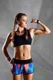 Den härliga unga kvinnan visar henne biceps Royaltyfri Foto