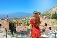 Den härliga unga kvinnliga modellen som tycker om sikt, fördärvar av gammalgrekiskateatern i Taormina med den Etna vulkan på bakg royaltyfria bilder