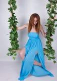 Den härliga unga långbenta redhaired kvinnan i en lång blått klär på en gunga, trägunga inställd från en rephampa, rep arkivfoton
