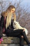 Den härliga unga le flickan strosar med den lilla vita hunden Tysk dvärg- Spitz pomeranian fotografering för bildbyråer