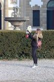 Den härliga unga le flickan strosar med den lilla vita hunden Tysk dvärg- Spitz pomeranian arkivbild