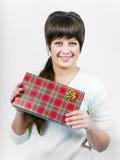 Den härliga unga lyckliga flickan med en gåva boxas Royaltyfria Bilder