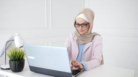 Den härliga unga muslim kvinnan arbetar på bärbara datorn på hennes arbetsplats stock video