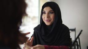 Den härliga unga muslimkvinnan i svart hijab talar till hennes oigenkännliga vän, medan sitta i coffee shop Kvinnor arkivfilmer