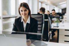 Den härliga unga och lyckade le flickan sitter på tabellen i hennes kontor Affärskvinna arkivfoton