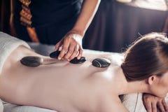 Den härliga, unga och sunda kvinnan har varm stenmassage brunnsort 7 arkivfoto