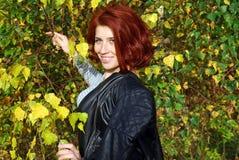 Den härliga unga röda flickan poserar nära höstträd Arkivfoton