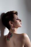 Den härliga unga sexiga flickan med kort hår med tatueringen på hans baksida är mot väggen med ledsna kala skuldror Arkivfoton
