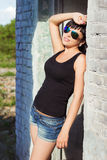 Den härliga unga sexiga flickan med långt hår i en solig sommardag i kortslutningar som står i den nya luften i solglasögon, near Arkivbild
