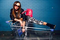 Den härliga unga sexiga flickan som har roligt sammanträde i near blå vägg för shoppingspårvagnvagn i solglasögon, rosa färg vand royaltyfria foton