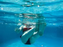 Den härliga unga spensliga attraktiva flickan, en kvinna i röda och svarta baddräktbad, badar under det blåa vattnet, undervatten arkivfoton