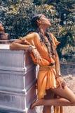 Den härliga unga trendiga kvinnan med utgör och stilfull bohotillbehör som poserar på naturlig tropisk bakgrund arkivbild