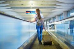 Den härliga unga turist- flickan med ryggsäcken och bär på bagage i internationell flygplats Royaltyfri Fotografi