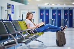 Den härliga unga turist- flickan med ryggsäcken och bär på bagage i internationell flygplats Royaltyfri Bild