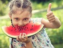 Den härliga ungeflickan som äter den stora röda vattenmelon med gyckel, blidkar blick Royaltyfri Foto
