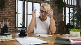 Den härliga upptagna affärskvinnan skriver att anmäla i dagbokdrinkkaffet som sitter bak skrivbordet i inrikesdepartementet arkivfilmer