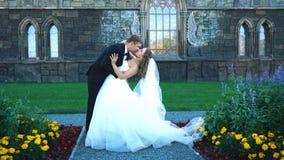 Den härliga ursnygga bruden och brudgummen som går i soligt, parkerar och att kyssa lyckliga brölloppar som kramar i gräsplan, ar lager videofilmer