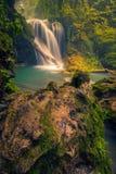 Den härliga vattenfallet med en träjournal och ett fuktigt vaggar i förgrunden royaltyfri foto