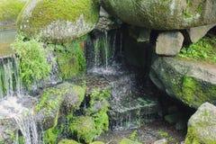 Den härliga vattenfallet med strålar av vatten på vaggar Royaltyfri Foto