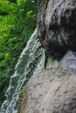 Den härliga vattenfallet med strålar av vatten på vaggar Royaltyfri Fotografi