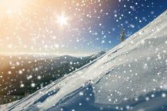 Den härliga vintern landscape Brant bergkullelutning med vit djup snö, avlägsen bergskedjapanorama, stora snöflingor och arkivbilder