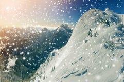 Den härliga vintern landscape Brant bergkullelutning med vit djup snö, avlägsen bergskedjapanorama, stora snöflingor och arkivfoton