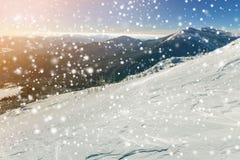 Den härliga vintern landscape Brant bergkullelutning med vit djup snö, avlägsen bergskedjapanorama, stora snöflingor och royaltyfria bilder